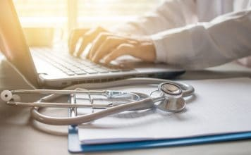 Stethoscope on prescription clipboard and Doctor working an Laptop on desk in hospital, Healthcare and medical concept, vintage color, selective focus