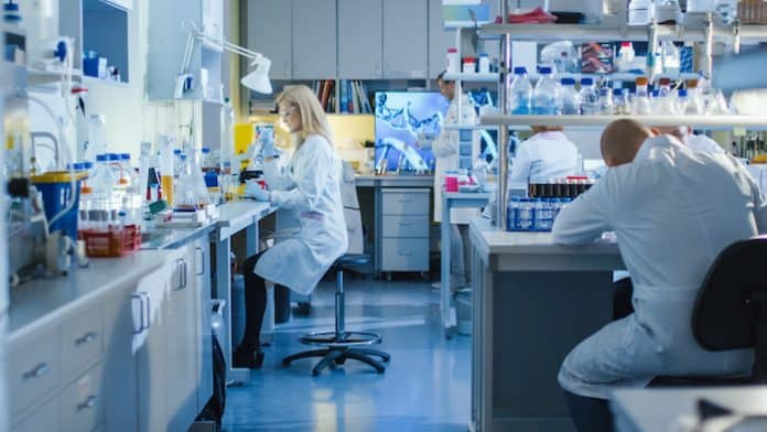 Genetic Research Scientists Work with Medical Equipment in a High Tech Research Laboratory. Female Scientist is using a Micro Pipette While Working with Colleagues.