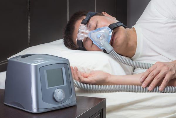 Asian man with sleep apnea using CPAP machine, wearing headgear mask connecting to air tube