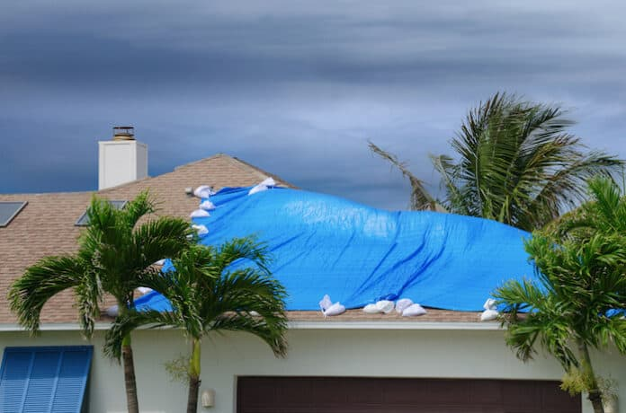 Storm damaged roof on house with a blue plastic tarp over hole in the shingles and rooftop.