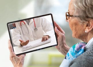 Mature adult women consults a e-health doctor with tablet computer sitting in soft chair. In touchscreen, male doctor