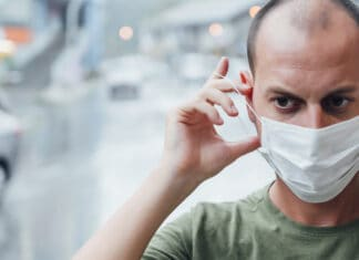 Man putting on a mask with a worried face. Virus concept