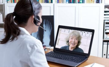 Female doctor in her surgery office with headset in front of her laptop, an x-ray of a foot in hand, talking with a senior patient, telemedicine concept