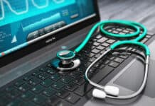Creative abstract healthcare, medicine and cardiology tool concept: laptop or notebook computer PC with medical cardiologic diagnostic test software on screen and stethoscope on black wooden business office table with selective focus effect