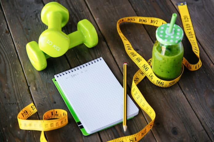 Detox green smoothie, blank copyspace notebook and measuring tape on wooden table for dieting and healthy fitness nutrition concept. Workout routine and diet planning.
