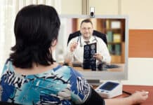 Middle-aged cardiologist sits face to face with online female patient which measures her blood pressure. Handsome virtual doctor attentively reviews brain x-ray results with her. Horizontal shot on blurry indoors background