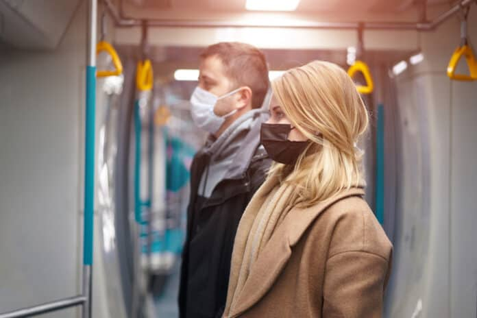 Side view of young man and woman in medical masks standing next to subway car. Coronavirus pandemic.