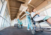 Low angle view of female nurses pushing patients on wheelchairs with doctor walking at corridor in hospital