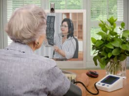 Old retired woman sitting in front of monitor. She has just sent her blood pressure and pulse information to virtual doctor. At the same time, telemedicine physician is looking at her CT x-ray on the screen