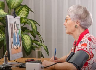 Old grey haired wom an is measuring blood pressure by herself during virtual doctor visit. Glasses senior woman sitting opposite monitor. On the screen, telehealth doc is consulting her. Side shot
