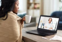 healthcare, technology and people concept - african american sick woman in blanket having video call with doctor on laptop computer and drinking tea at home