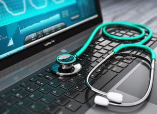 Creative abstract healthcare, medicine and cardioloagy tool concept: laptop or notebook computer PC with medical cardiologic diagnostic test software on screen and stethoscope on black wooden business office table with selective focus effect