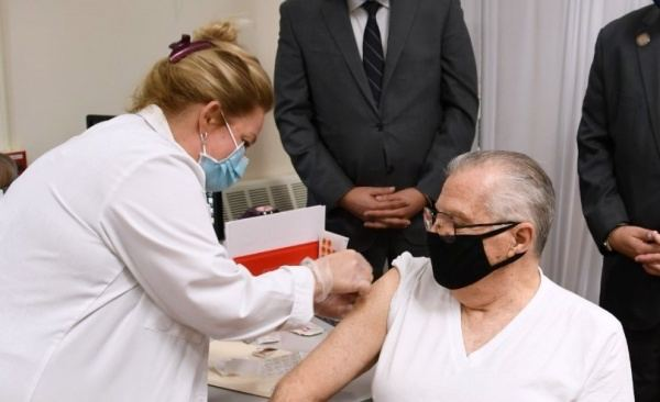 A man getting vaccinated by a nurse