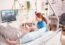 Female doctor in nursing home with senior woman watching tv.