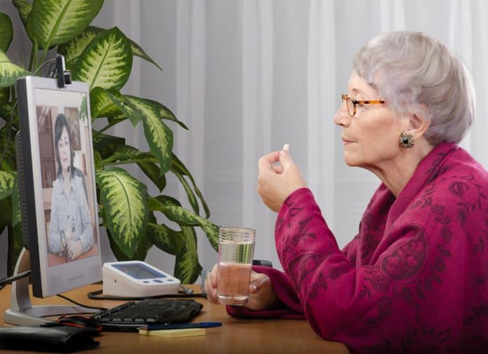 Old woman taking a pill during medical consultation online. Grey haired woman in crimson cape sitting opposite monitor. On the screen doctor is consulting her. Side shot