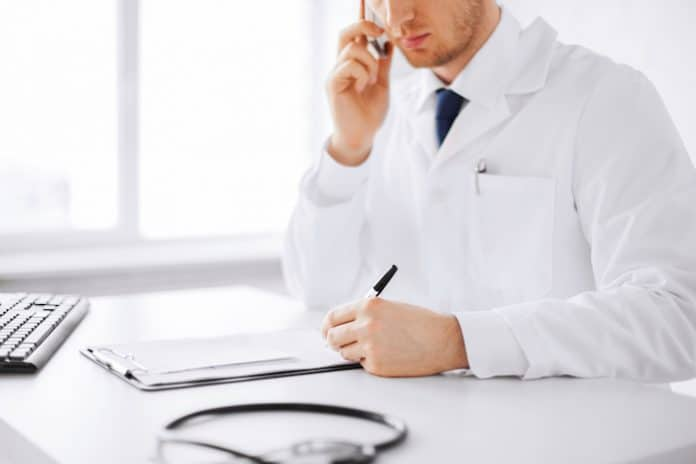 healthcare, hospital and medical concept - male doctor writing prescription paper and capsules