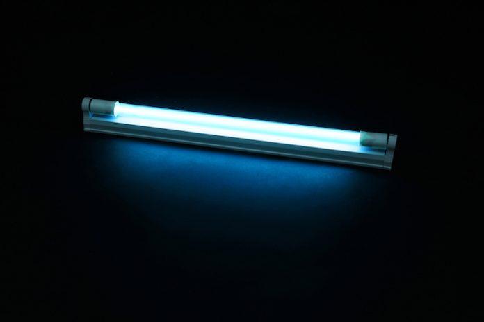 Modern ultraviolet lamp glowing on black background