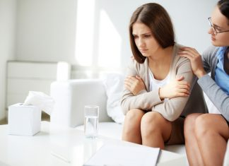 Young woman consoling a crying female friend while sitting on sofa