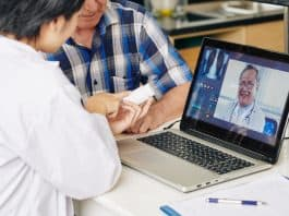 Medical nurse consulting with general practitioner via video call and recommending tablets to senior patient